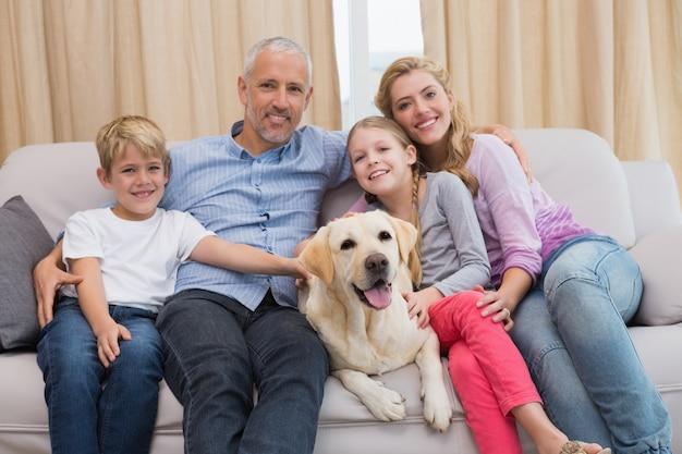 Pais e seus filhos no sofá com labrador