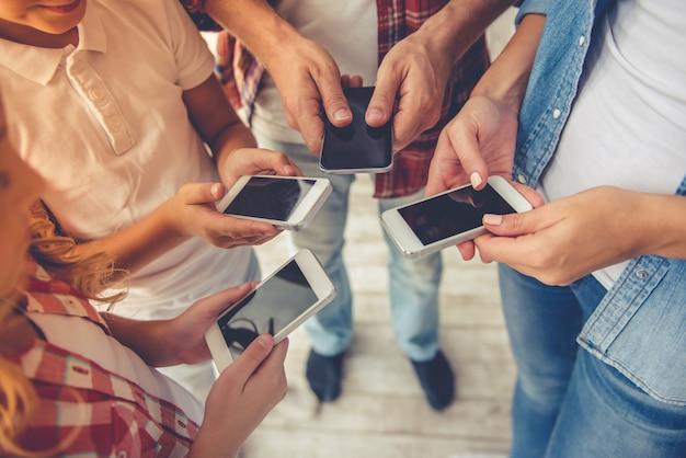 Pais e seus filhos usando smartphones.