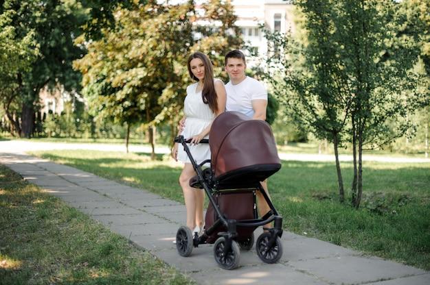 Pais e sua filha pequena na carruagem de bebês