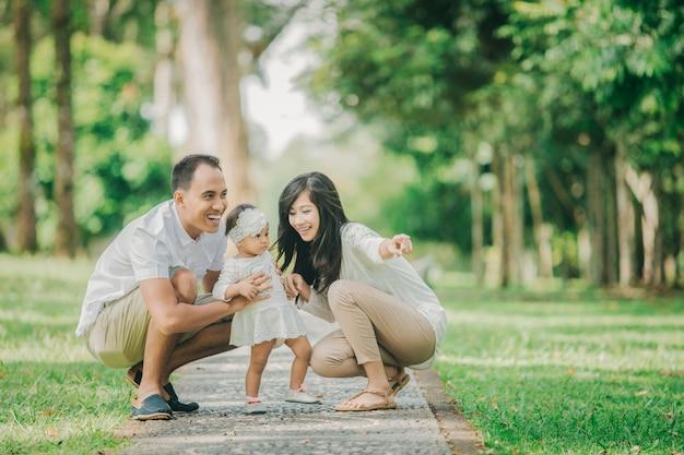 Pais em roupas brancas andando com sua filha bebê no parque