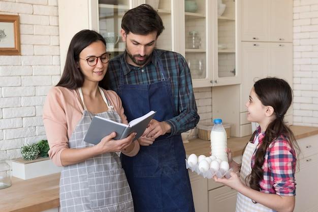 Pais ensinando menina a cozinhar