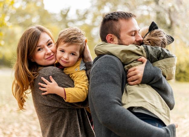 Pais felizes abraçando crianças em foto média