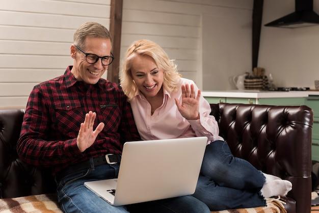 Pais felizes, acenando para o laptop no sofá