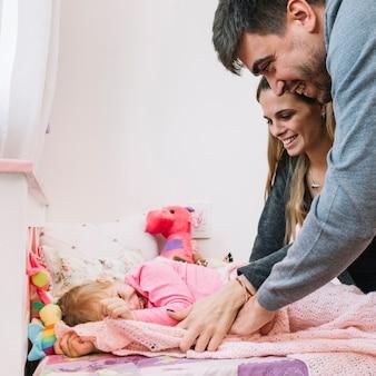 Pais felizes andando com a filha na cama
