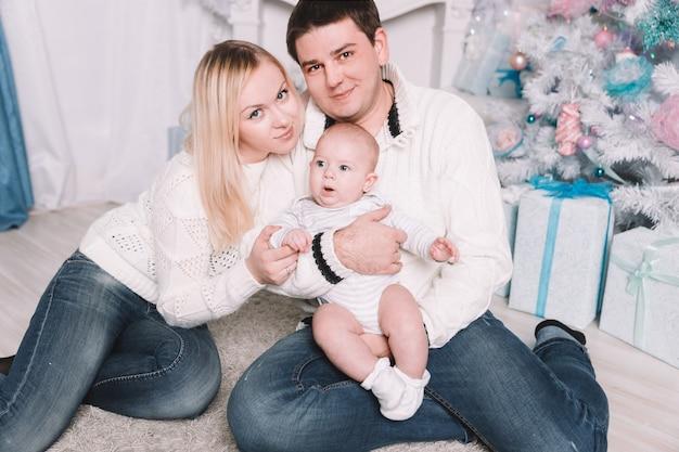 Pais felizes beijam seu bebê na véspera de natal. o conceito de felicidade