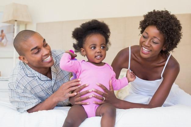Pais felizes brincando com bebé na cama juntos