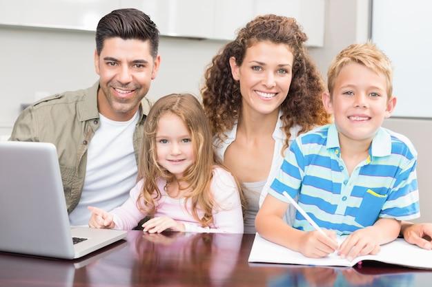 Pais felizes colorindo e usando laptop com seus filhos pequenos