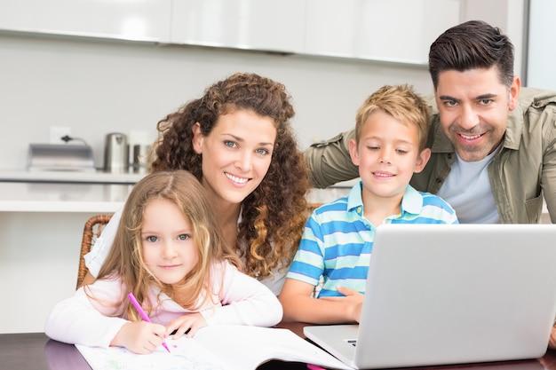 Pais felizes colorindo e usando laptop com seus filhos