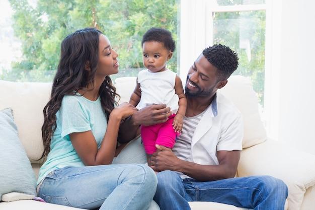 Pais felizes com a menina no sofá