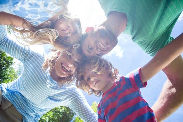 Pais felizes com crianças formando amontoados no quintal