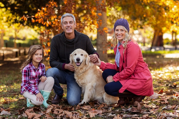 Pais felizes com filha e cachorro no parque