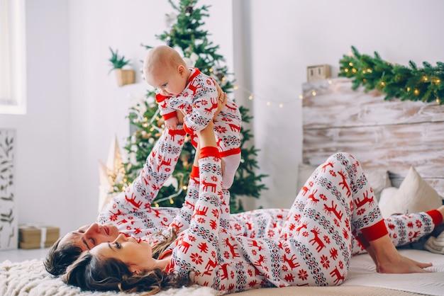 Pais felizes com sua filha em roupas de férias com veados impressos e flocos de neve se divertindo na cama no quarto acolhedor com uma árvore de natal