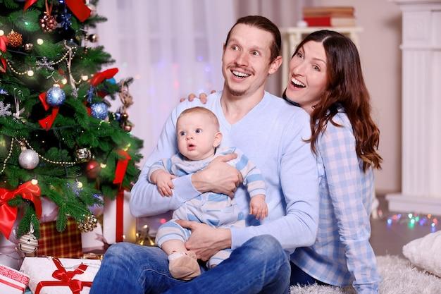 Pais felizes com um bebê perto da árvore de natal no chão da sala decorada