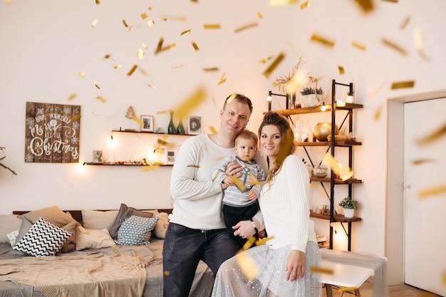 Pais felizes com uma criança linda juntos em um estúdio maravilhoso, se abraçando, olhando para a frente e posando