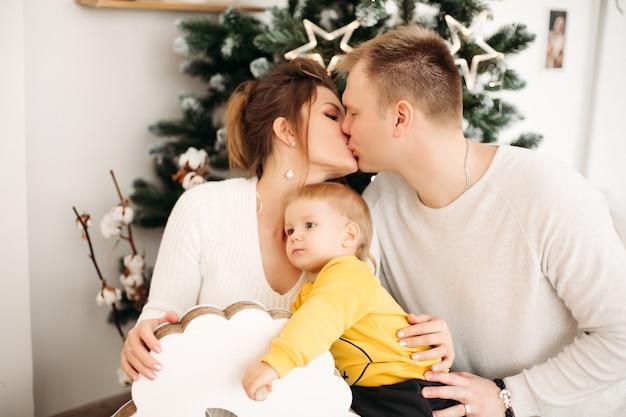 Pais felizes e apaixonados se abraçando e se beijando, sentados no fundo perto da árvore de natal com o filho pequeno