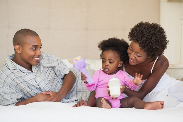 Pais felizes e baby girl sentados na cama juntos