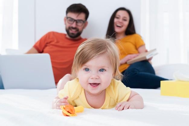 Pais felizes e bebê na cama