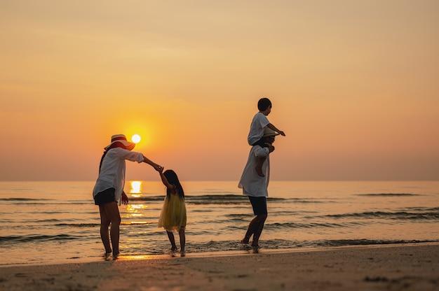 Pais felizes e criança se divertindo jogando areia nas férias de verão na praia. viagem
