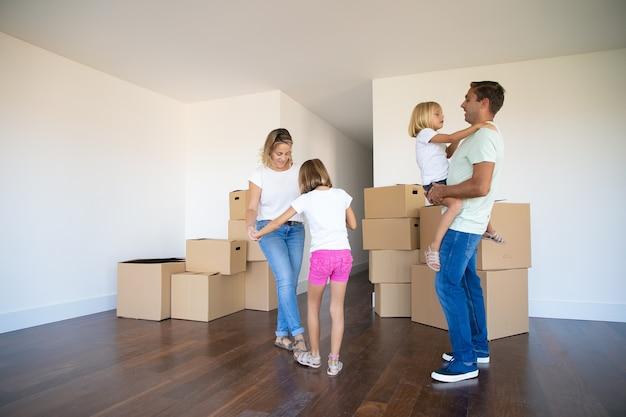 Pais felizes e duas meninas dançando e se divertindo perto de pilhas de caixas enquanto se mudam para um novo apartamento