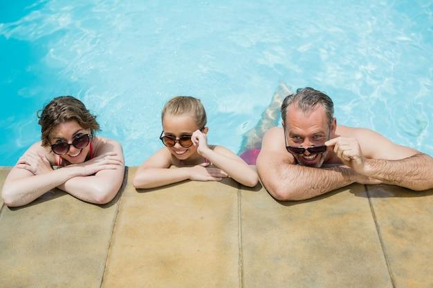 Pais felizes e filha relaxando na piscina