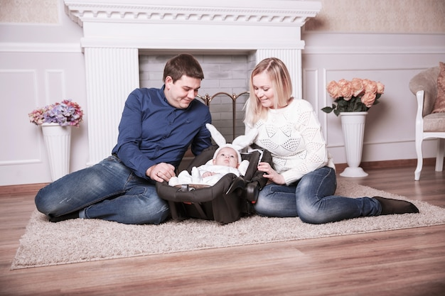 Pais felizes e filho de um ano em uma roupa de coelhinho na sala de estar