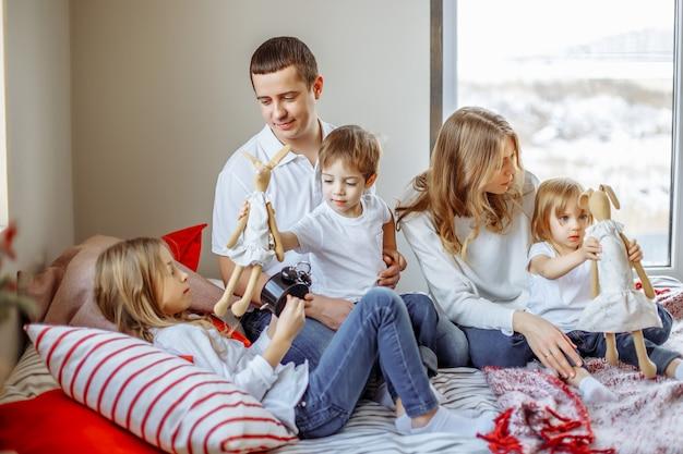 Pais felizes e filhos desfrutando de manhã na cama