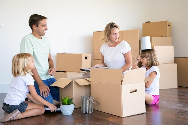 Pais felizes e meninas se divertindo enquanto desempacotam coisas em um apartamento novo, sentados no chão e tirando objetos de caixas abertas