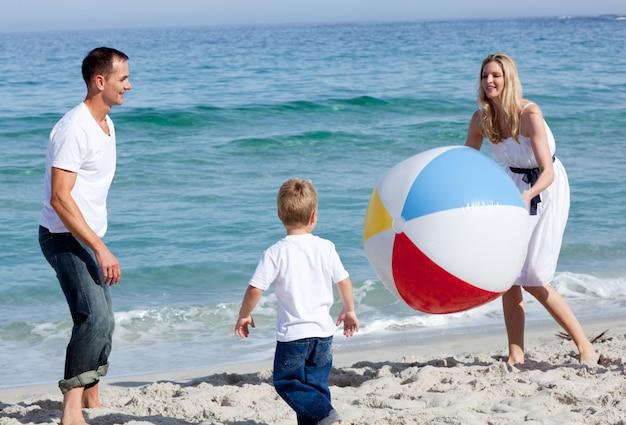 Pais felizes e seu filho brincando com uma bola