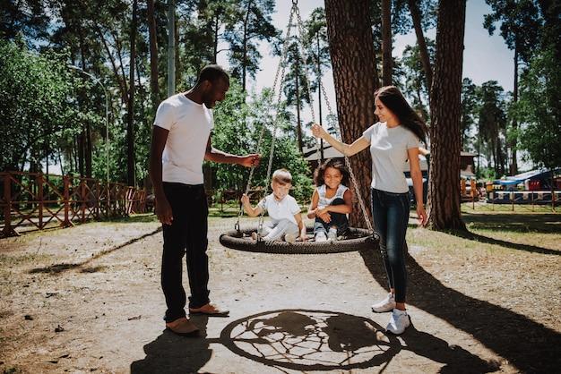 Pais felizes, empurrando as crianças no balanço no parque infantil
