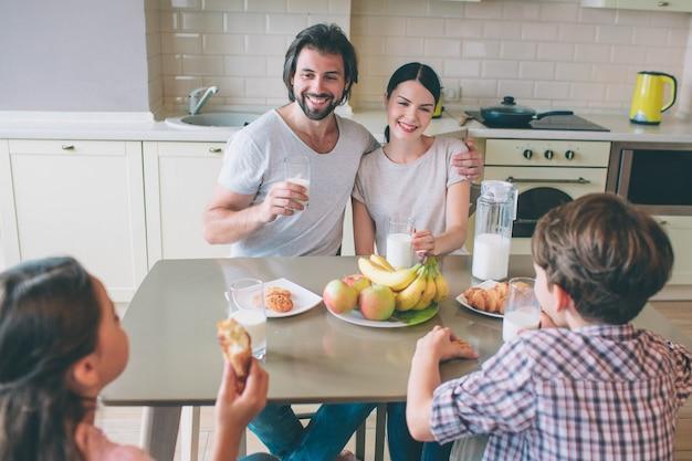 Pais felizes estão sentados na frente dos filhos e se abraçando. eles seguram copos de leite. as crianças estão comendo biscoitos. eles estão passando tempo juntos.