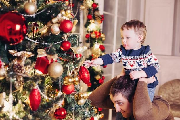 Pais felizes, mostrando a decoração de natal na árvore para o filho pequeno.