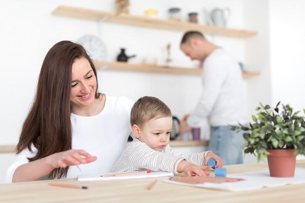 Pais felizes na cozinha com criança