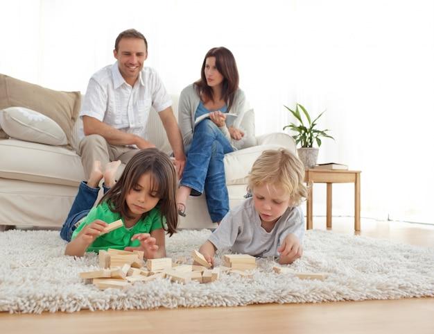 Pais felizes no sofá olhando seus filhos brincando no chão