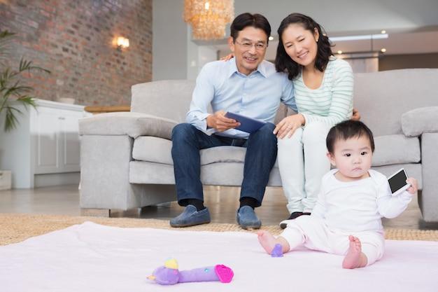 Pais felizes, olhando para a filha do bebê na sala de estar