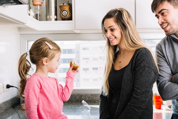 Pais felizes olhando para sua filha segurando o bolinho na cozinha