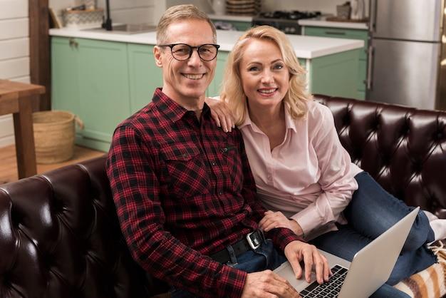 Pais felizes posando com laptop no sofá