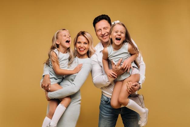 Pais felizes seguram seus filhos nos braços e sorriem em um fundo amarelo. uma família emocional de quatro