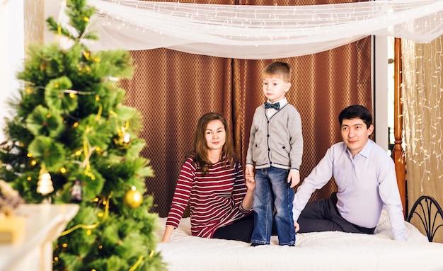 Pais felizes sorrindo e criança em casa comemorando o ano novo. árvore de natal.