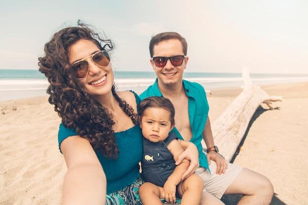 Pais felizes, sorrindo e tomando selfie na praia.