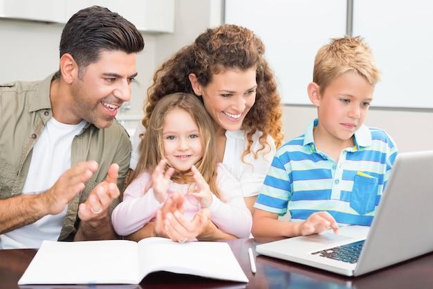Pais felizes usando laptop com seus filhos pequenos