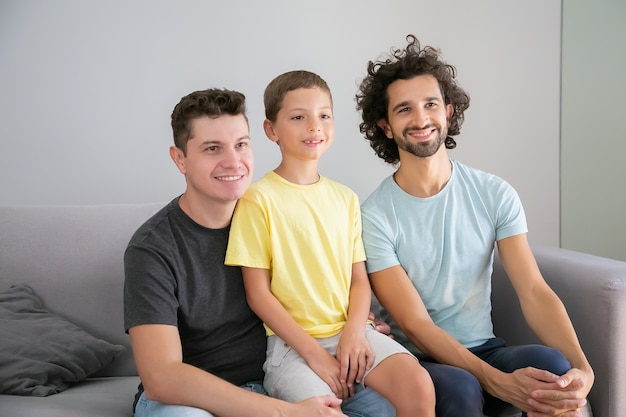 Pais gays felizes e criança sentada no sofá em casa, sorrindo e olhando para longe. vista frontal. conceito de família e paternidade