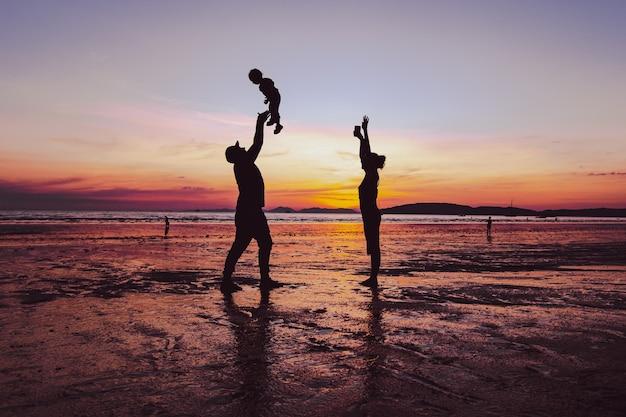 Pais gostando de jogar seu bebê para o alto com um pôr do sol incrível na praia