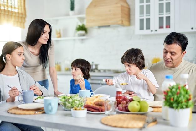 Pais hispânicos amorosos, cuidando de seus filhos pequenos enquanto almoçavam juntos em casa. infância, paternidade, conceito de cozinha latina
