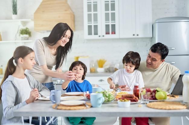 Pais hispânicos amorosos cuidando de seus filhos pequenos, entretendo-os enquanto almoçavam juntos em casa. infância, paternidade, conceito de cozinha latina