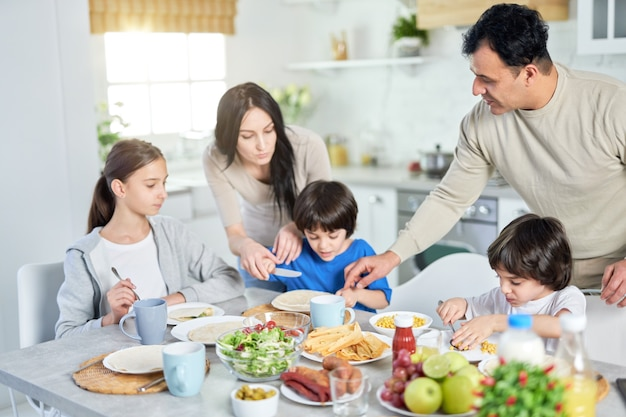 Pais hispânicos amorosos servindo seus filhos pequenos enquanto almoçavam juntos em casa. infância, paternidade, conceito de cozinha latina
