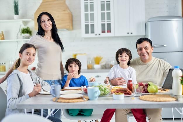 Pais hispânicos sorridentes, passando um tempo com seus filhos pequenos, tomando café da manhã juntos em casa. infância, paternidade, conceito de cozinha latina