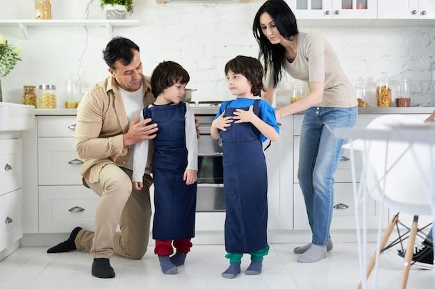 Pais hispânicos vestindo aventais em dois meninos gêmeos enquanto cozinham o jantar na cozinha de casa juntos. família feliz, filhos, conceito de cozinha
