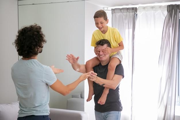 Pais homossexuais alegres e o filho jogando jogos ativos em casa, se divertindo. rapaz cavalgando no pescoço do homem e fechando os olhos do pai com as mãos. conceito de família e paternidade