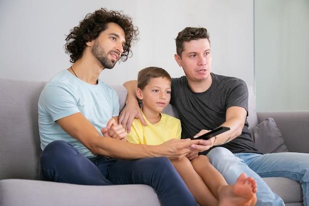 Pais homossexuais animados e filho assistindo programa de tv em casa, sentados no sofá da sala, se abraçando, usando o controle remoto, olhando para longe. conceito de entretenimento familiar e doméstico