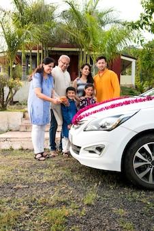 Pais indianos modernos com filhos dando as boas-vindas ao novo ca tradicionalmente, apresentando pooja